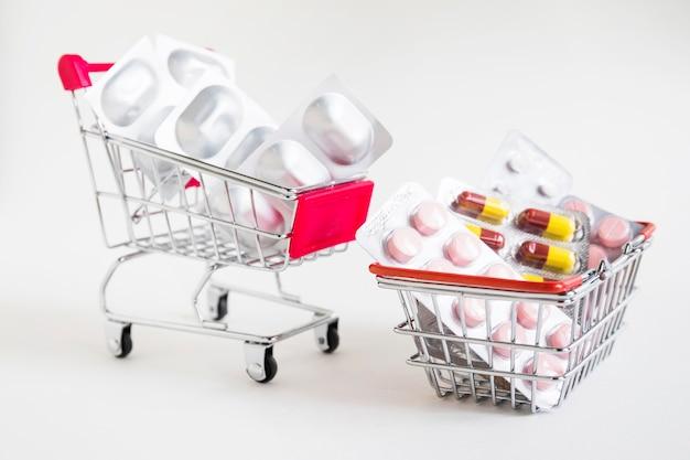 Carrelli della spesa con le medicine della bolla su fondo bianco