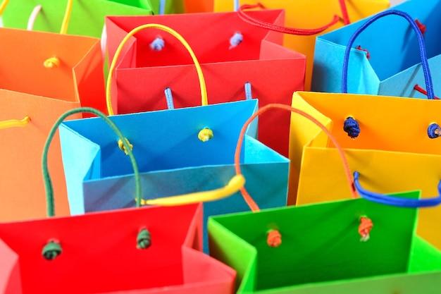 Primo piano variopinto dei sacchetti di carta di vendita di acquisto come fondo