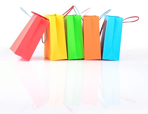 Primo piano variopinto dei sacchetti di carta di vendita di acquisto su un fondo bianco