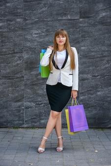 Concetto di acquisto. bella ragazza che tiene i sacchetti colorati dopo il successo dello shopping.