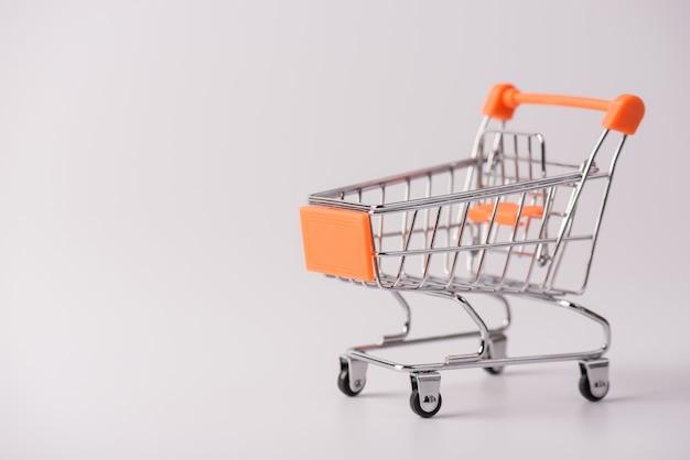 Concetto di acquisto. foto ravvicinata di un piccolo carrello a spinta con elementi arancioni isolati su sfondo grigio con spazio vuoto per la copia