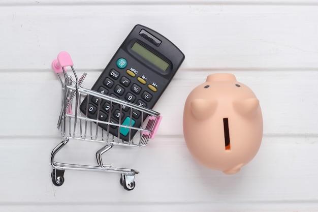 Concetto di acquisto, economia. salvadanaio con carrello per supermercati e calcolatrice su superficie di legno bianca. vista dall'alto