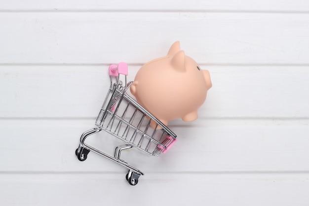 Concetto di acquisto, economia. salvadanaio con carrello per supermercati su superficie di legno bianca. vista dall'alto