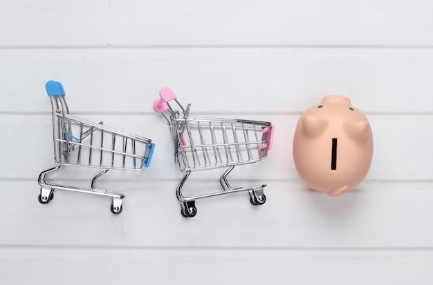 Concetto di acquisto, economia. salvadanaio con carrelli per supermercati su superficie di legno bianca. vista dall'alto