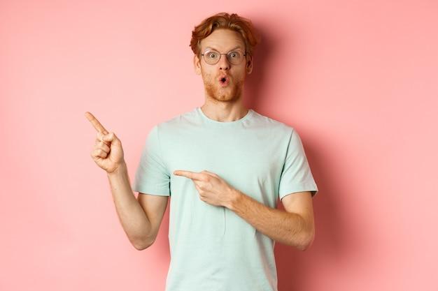 Concetto di acquisto. ritratto di uomo con barba e capelli rossi, con gli occhiali con t-shirt estiva, puntando il dito nell'angolo in alto a sinistra e dicendo wow impressionato, sfondo rosa.