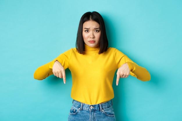 Concetto di acquisto. ragazza asiatica triste e preoccupata accigliata sciocca, puntando il dito verso il basso per errore, in piedi sconvolto su sfondo blu.