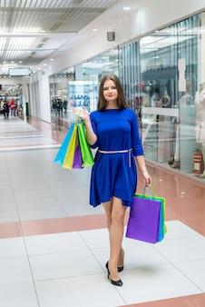 Concezione dello shopping, donna con borse nel centro commerciale
