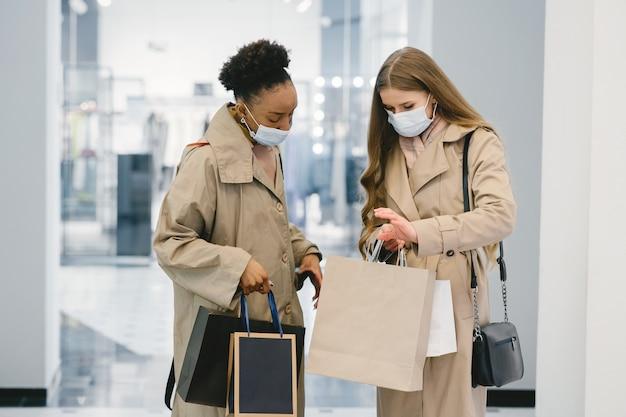 Giornata di shopping. concetto di coronavirus. donne con maschere mediche.