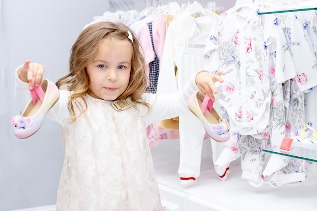 Shopping. sconti. bambina shopaholic. la ragazza sceglie le scarpe per il suo vestito. centro commerciale, shopping. emozioni