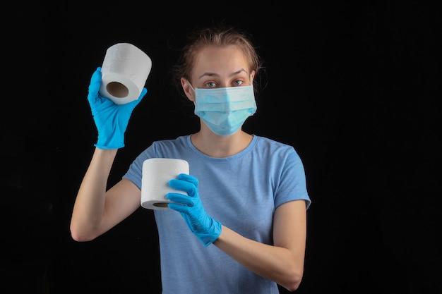 Shopping durante la pandemia 19-covid. la donna in mascherina e guanti medici tiene la carta igienica sulla parete nera.