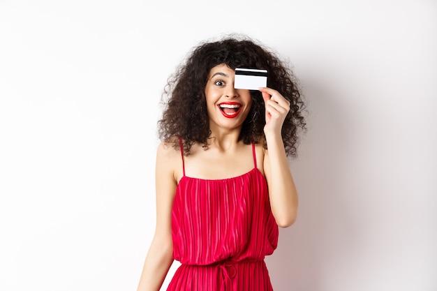 Shopping. eccitata ragazza riccia in abito rosso, mostrando la carta di credito in plastica e urla di gioia, stupita da sconti e prezzi, in piedi su sfondo bianco.