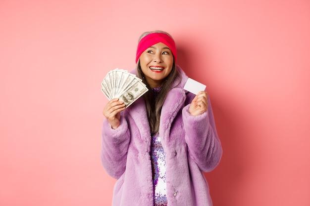 Shopping e concetto di moda. donna anziana asiatica alla moda che sogna negozi e vendite, con in mano denaro in dollari e carta di credito in plastica, sfondo rosa.