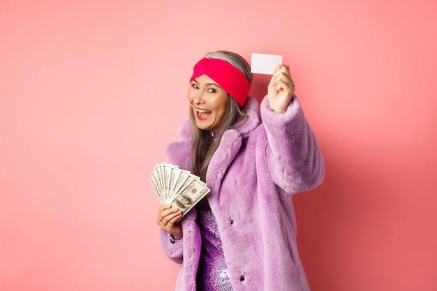 Shopping e concetto di moda. donna asiatica funky alla moda che mostra la carta di credito di plastica, pagando senza contatto, tenendo i soldi in altra mano, fondo rosa