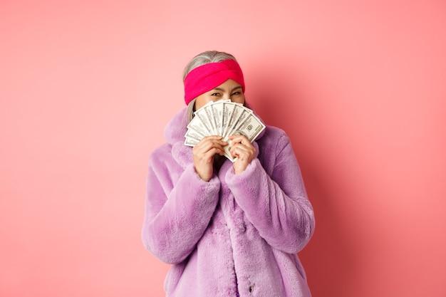 Shopping e concetto di moda. felice donna asiatica in abiti invernali alla moda, che tiene in mano soldi e li mostra alla telecamera, in piedi con dollari su sfondo rosa.