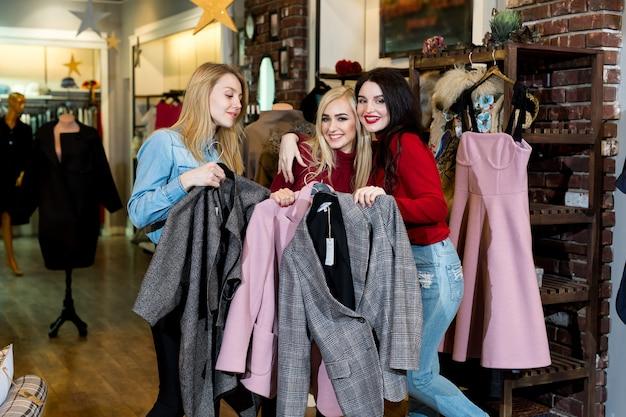 Shopping, moda e amicizia: tre amici sorridenti scelgono un tailleur in un negozio di abbigliamento e posano per la fotocamera.