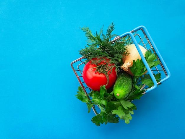 Metallo del carrello della spesa di acquisto sull'azzurro. concetto di cesto alimentare. avvicinamento. lay piatto. messa a fuoco morbida selettiva. . copia del testo spazio.