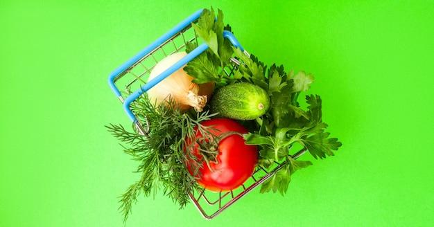 Metallo del carrello della drogheria di acquisto su verde. concetto di cesto alimentare. avvicinamento. lay piatto. messa a fuoco morbida selettiva. . copia del testo spazio.