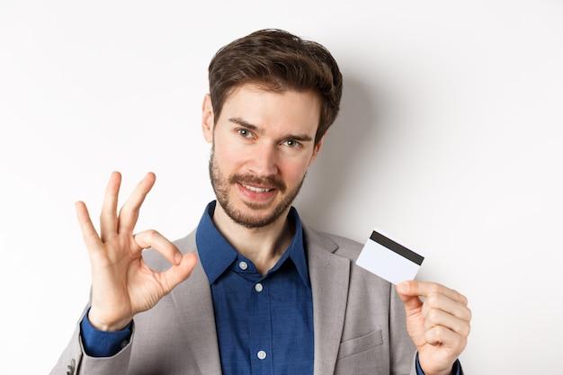 Shopping. uomo bello che mostra segno giusto e carta di credito in plastica, tutto sotto controllo, nessun gesto di preoccupazione, sfondo bianco.