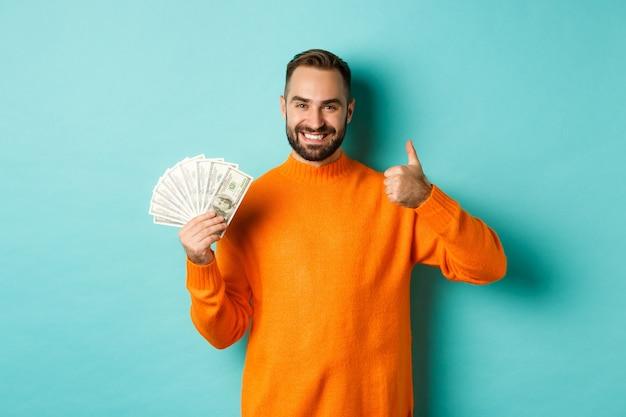 Shopping. uomo felice che mostra pollice in su e soldi in dollari, consigliando prestiti bancari o crediti, in piedi su sfondo azzurro.