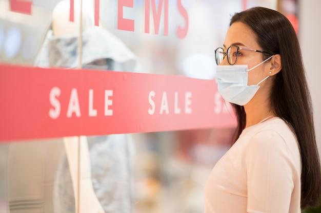 Lo shopping è un grande passatempo nelle regioni asiatiche donna che indossa lo shopping maschera nel grande magazzino