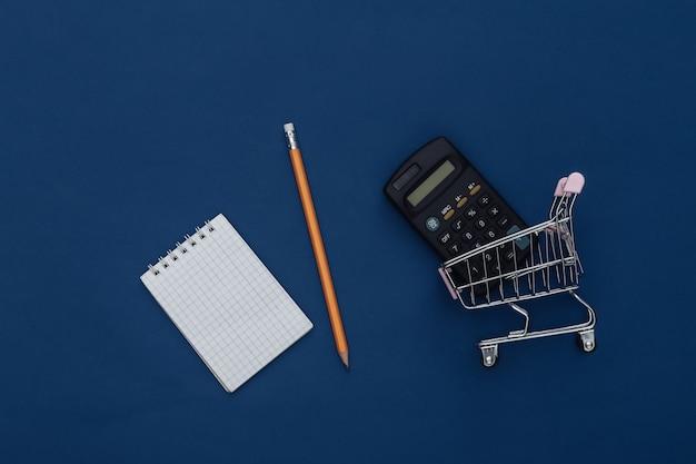 Lista della spesa. carrello della spesa con calcolatrice, taccuino e matita su sfondo blu classico. colore 2020. vista dall'alto