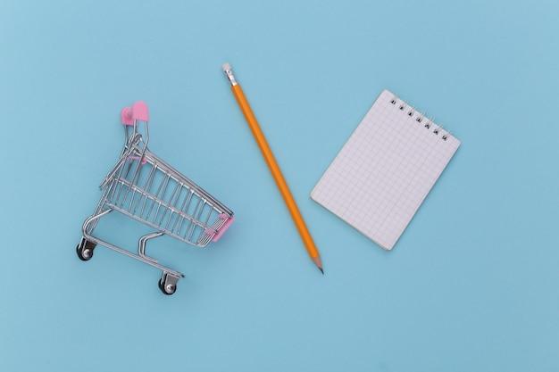 Lista della spesa. carrello della spesa con taccuino e matita su sfondo blu. vista dall'alto