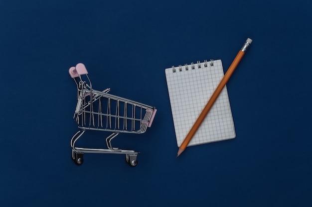 Lista della spesa. carrello della spesa con taccuino e matita su sfondo blu classico. colore 2020. vista dall'alto