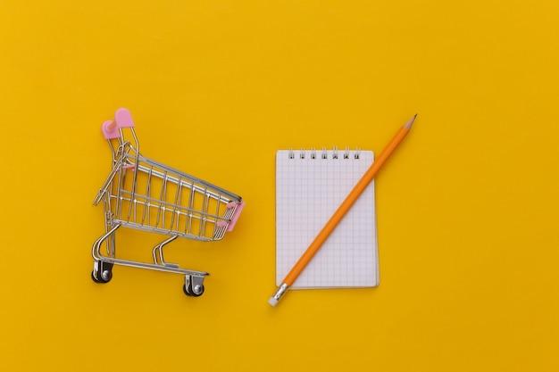 Lista della spesa. carrello della spesa con taccuino e matita su sfondo giallo. vista dall'alto