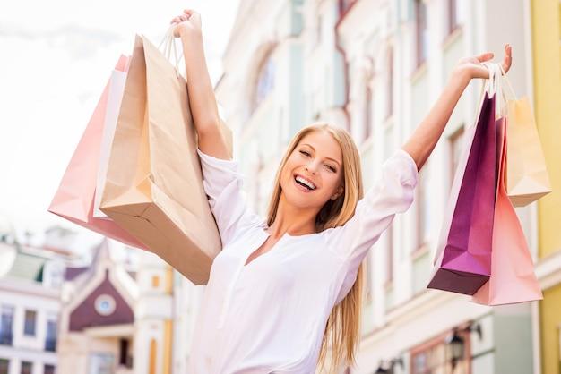 Lo shopping la rende felice. attraente giovane donna che tiene le borse della spesa e sorride mentre sta in piedi all'aperto