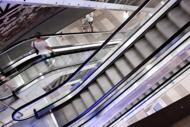 Centro commerciale con scale mobili in movimento e persone in movimento.
