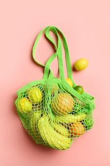 Shopping bag a rete con friuts, limone, arancio su giallo. concetto di rifiuti zero. zero sprechi. prodotti vegani sani, borsa a rete, zenzero, insalata, verdure. stile di vita sostenibile. vista dall'alto