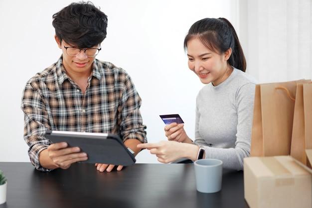 Concetto di shopping online una coppia che si gode lo shopping online e acquista molte cose con una carta di credito.