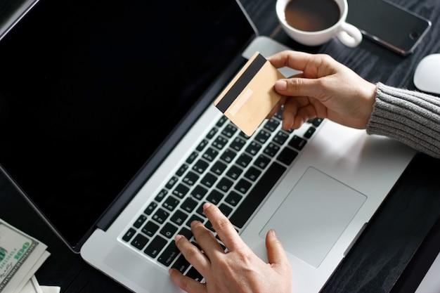 Shopping online concetto. donna che tiene in mano carta di credito oro e shopping online