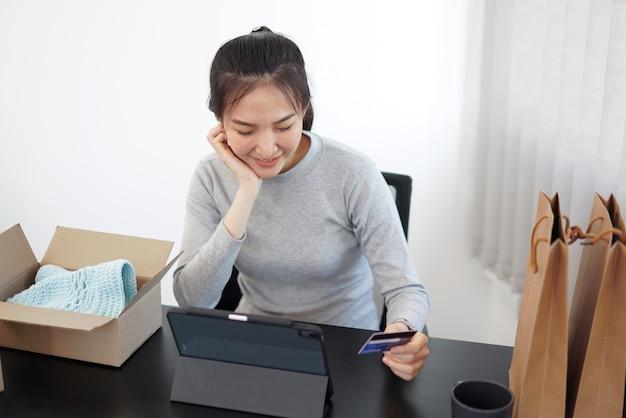 Concetto di shopping online una giovane donna che utilizza la sua carta di credito per facilitare un acquisto online nell'applicazione di shopping online.