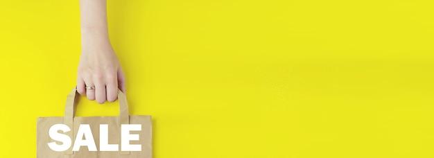 Shopping o concetti di negozio online su internet. borsa per la spesa in carta marrone riciclata in mano con testo ologramma vendita su sfondo giallo, piatto. concetto di vendita estiva. concetto di servizio di consegna.