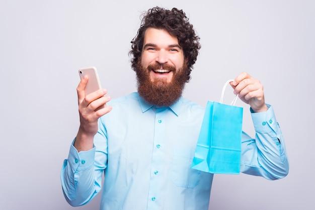 Lo shopping online è fantastico, giovane uomo barbuto in camicia blu usando lo smartphone e tenendo la borsa della spesa blu