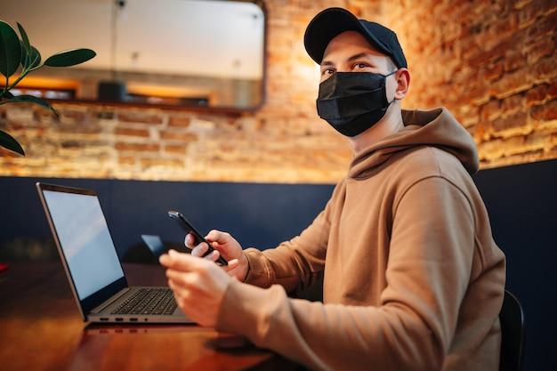 Acquisti e pagamenti online tramite cellulare, laptop e carta di credito. uomo che indossa una maschera durante la pandemia
