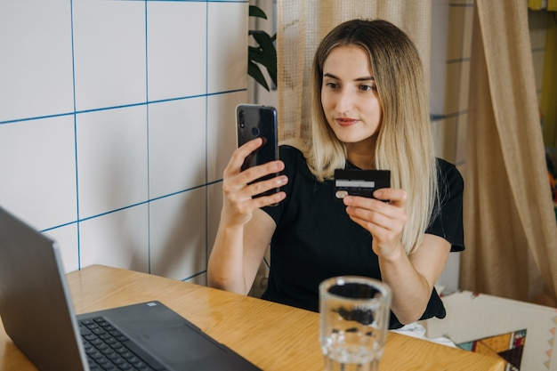 Acquisti online esperti di pagamenti rateali donna a casa utilizzando carta di credito e laptop per
