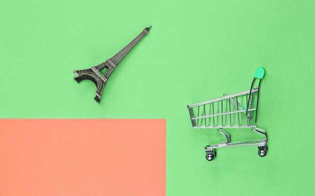 Shopping a parigi concetto minimalista. carrello della spesa, figurina della torre eiffel su sfondo color pastello. vista dall'alto