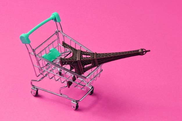 Shopping a parigi concetto minimalista. carrello della spesa, figurina della torre eiffel su sfondo rosa.