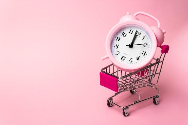 Shopping, acquisti, supermercato un carrello del supermercato in metallo in miniatura con sveglia all'interno