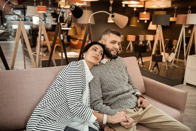 Risultati di acquisto. donna dai capelli scuri in giacca a righe che riposa sulla spalla del marito dopo una lunga giornata nel negozio di mobili