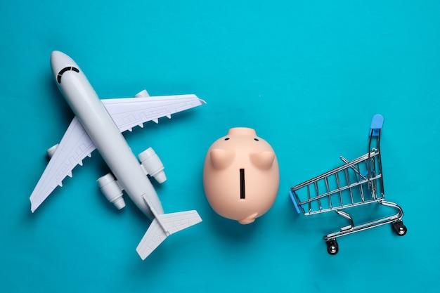 Shopping ancora in vita. carrello della spesa, figurina dell'aeroplano del salvadanaio su un blu