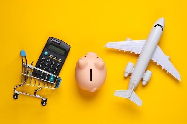 Shopping ancora in vita. carrello della spesa, figurina di aeroplano salvadanaio, calcolatrice su giallo