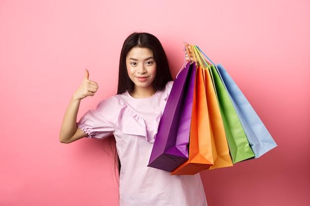 Shopping. ragazza alla moda che mostra i sacchetti di carta colorati e il pollice in su, consiglia sconti del negozio, in piedi su sfondo rosa.