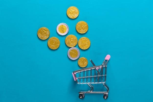Tema di acquisto. mini carrello per supermercati con monete su blu