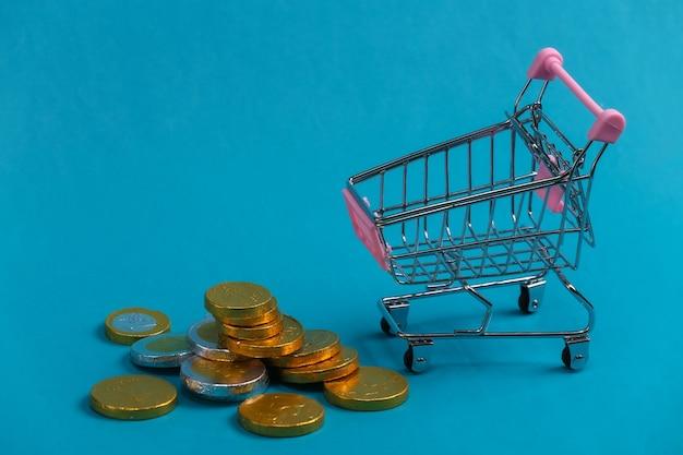 Tema di acquisto. carrello mini supermercato con monete sul bue.