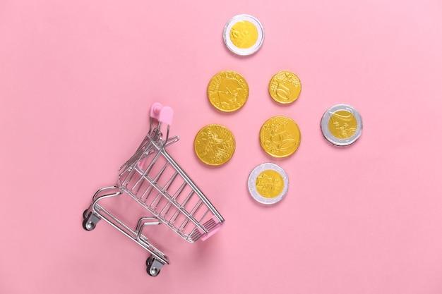 Tema di acquisto. mini carrello per supermercati con monete su rosa.