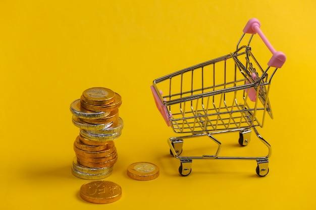 Tema di acquisto. carrello mini supermercato con monete su giallo.