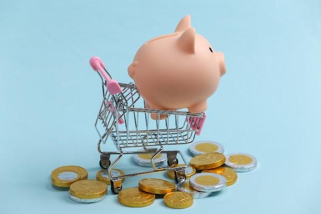 Tema di acquisto. mini carrello per supermercati con salvadanaio e monete sul blu.